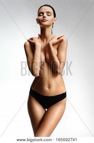 Perfect young woman posing topless on white background. Photo slim tanned of girl with slim toned body. Beauty and body care concept
