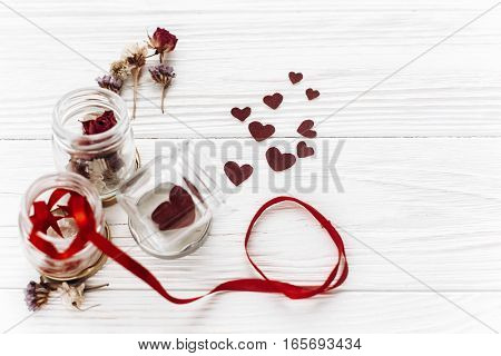 Happy Valentine Day. Stylish Hearts In Glass Jar And Roses And Ribbons On White Wooden Background. U