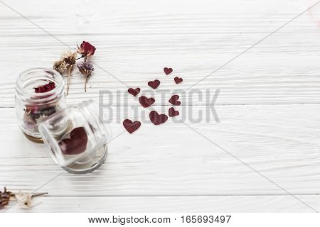 Happy Valentine Day. Stylish Hearts In Glass Jar And Roses On White Wooden Background. Unusual Card.