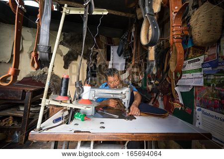 July 26 2016 Riobamba Ecuador: a man is sewing leather wooly chaps in his small saddlery shop near the city centre