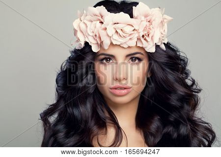 Beautiful Model Woman in Flowers Wreath. Perfect Model with Natural Makeup Healthy Skin Curly Hair and Roses Flowers