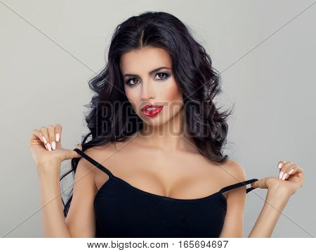 Beautiful Model with Curly Hairstyle Red Lips Makeup and Black Top. Perfect Brunette Woman with Healthy Hair and Makeup