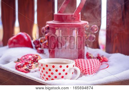 Cozy Scene with Vintage Candle Lamp, Heart, Hot Cup of Tea on the Snow, Pomegranate, Daylight, Outdoors. Copy space, Selective focus, Toned.