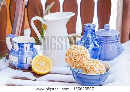 Cozy Scene with Vintage Blue Cups, Vases, Decanters in the Snow, Lemon, Cookies. Daylight, Outdoors. Copy space, Selective focus