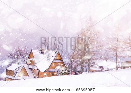 Winter snowy landscape with mountain village. Nature scene with snow and sun flare, sunlight, daylight, outdoors. Abstract blurred background. Copy space, Selective focus, toned.