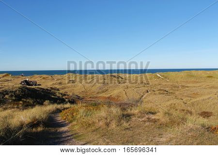Crystal Blue Waters in the Horizon behind Small Sandy Hills under a Clear Sky.