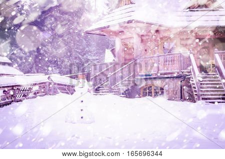 Winter snowy wooden house and a snowman in the yard. Nature scene with snow and sun flare, sunlight, daylight, outdoors. Abstract blurred background.