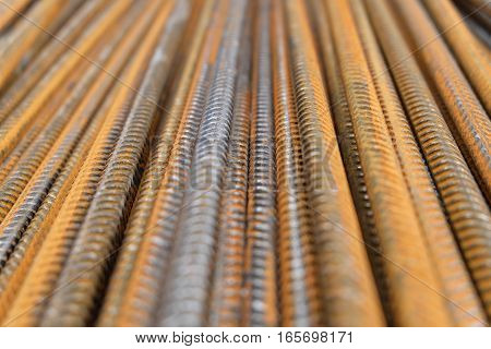Rusty division rebar at an industrial building construction site. The rust is clearly visible on the deformed reinforcement bars which are stacked to be used as armature in cement. poster
