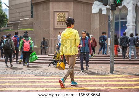 Hong Kong, China - December 6, 2016: Typical Asian woman in yellow along intersection in Times Square.Causeway bay is one of most attractive areas for tourists visiting Hong Kong and good for shopping