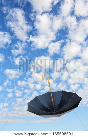 Overturn Black Umbrella flies in sky against of pure white clouds.Mary Poppins Umbrella.