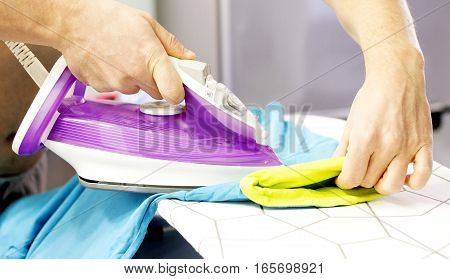Male hands ironing a t-shirt at home on board.