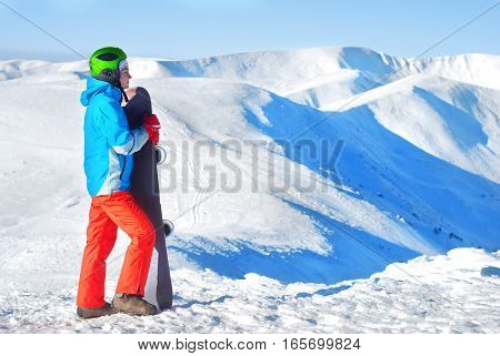 girl standing on a mountain top with snowboard in the hands