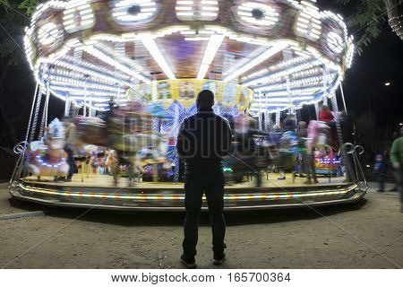 Carousel in motion with immobile man at Christmas Fair