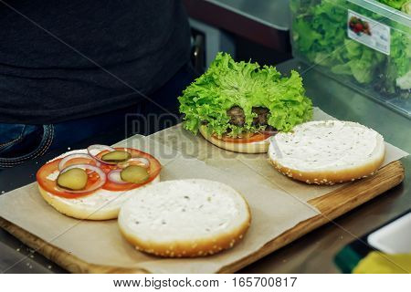 Process Of Making Burger. Cooking Hamburgers And Cheeseburgers, Putting Ingridients On Wooden Desk.
