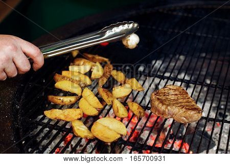Potatos Meat Garlic And Tomato Pepper Grilling. Chef Working With Tongs. Catering In Food Court At M