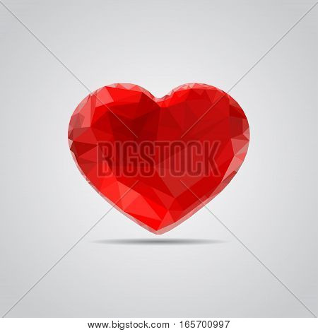 Red heart in polygonal style with shadow on a gray background