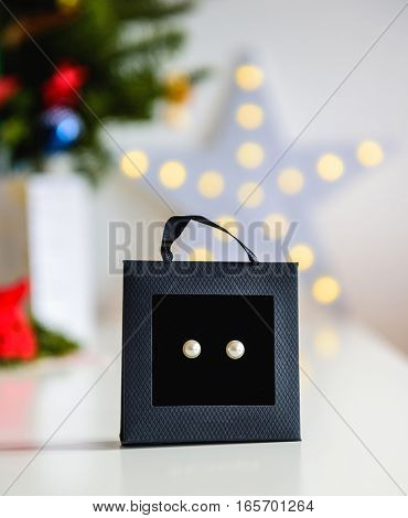 Pearl earrings in luxury fun box in shape of a bag with defocused holiday bacground ready for the birthday wedding christmas new year anniversary