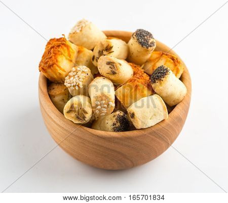 Salty party snacks in wooden bowl. Closeup details.