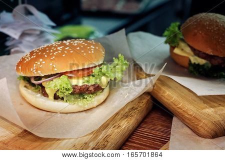 Yummy Burger. Serving Cheeseburger Or Hamburger With Salad And Tomatoes Onion And Cheese On Wooden D