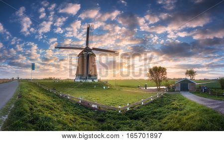 Windmill At Sunrise In Netherlands. Beautiful Old Dutch Windmill