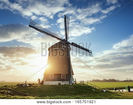 Windmill And Silhouette Of A Man At Sunrise In Netherlands