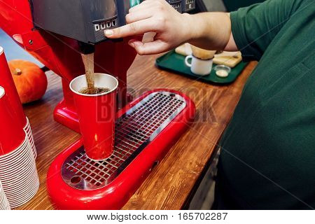 Hand Pouring Cola In Red Cup. Stylish Soda Machine On Wooden Desk. Take To Go. Catering In Food Cour