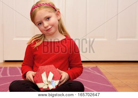 adorable school age girl wearing red and holding Valentine's Day gift