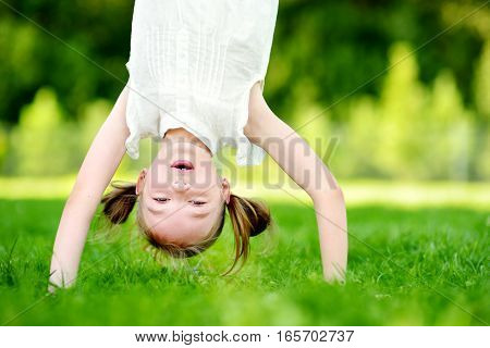 Happy Young Child Playing Head Over Heels On Green Grass
