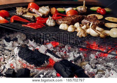 Juicy Vegetables And Meat Grilling. Beef Steak Mushrooms Corn Pepper Zucchini Tomatoes Garlic On Gri