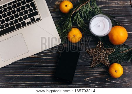 Laptop And Phone With Empty Screen For Christmas Seasonal Advertising On Background Of Green Branche
