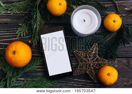 Christmas Advertising Concept. Flat Lay Phone With Empty Screen On Seasonal Background Of Green Bran