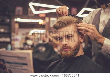 Handsome bearded man is reading a newspaper while getting haircut by hairdresser at the barbershop