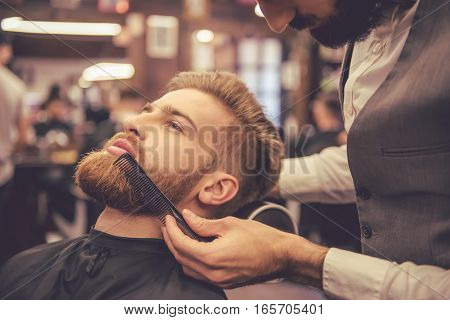 Handsome bearded man is getting beard hairstyle by hairdresser at the barbershop