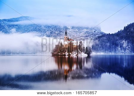 Winter landscape Bled Lake. Travel Slovenia Europe. Bled Lake one of most amazing tourist attractions. View on snowy Island with Catholic Church in Bled Lake.