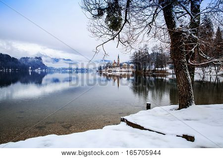 Winter landscape Bled Lake. Travel Slovenia Europe. Bled Lake one of most amazing tourist attractions. View on Island with Catholic Church in Bled Lake with Castle and Mountains in Background.