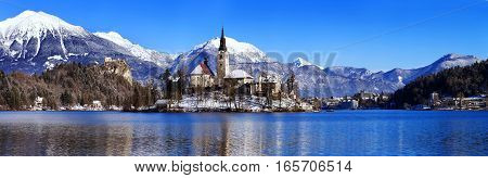 Travel Slovenia Europe. Winter landscape Bled Lake. Bled Lake one of most amazing tourist attractions. View on Island with Catholic Church in Bled Lake with Castle and snowy Alps in Background.
