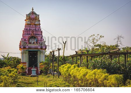 Ancient small temple against trees and bushes in Goa, India