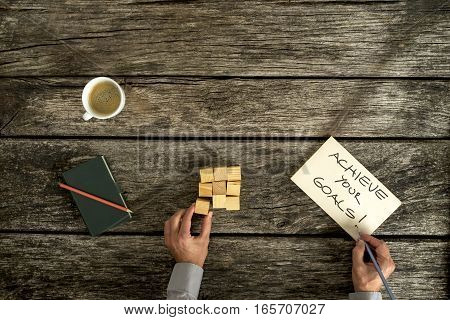 Overhead view of businessman writing achieve your goals sign on desk while solving puzzle.