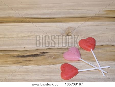 Yummy lollipop hearts on wooden background for Valentine's Day.  Space for text.
