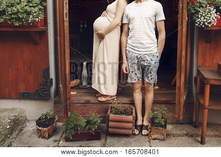 Stylish Family Expecting For A Baby And Posing On Background Of Flowers And City Street. Pregnant Wo