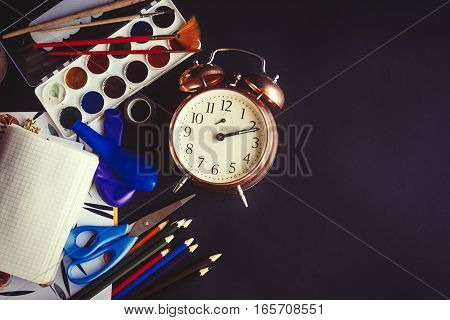 Colorful Pencils Paints Brushes Scissors And Notebook With Old Clock On Chalkboard Background, Space