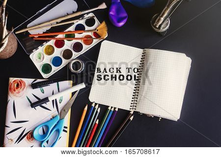Back To School Concept Text Chalk On Board, Colorful Pencils Paints Brushes Scissors And Notebook, S