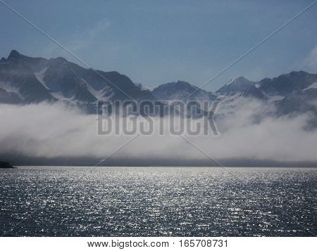 Beautiful view of snowy mountains through the fog on the beach in Seward Alaska. Calm, peaceful trip to the ocean in the morning with sun glistening on the water.
