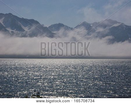 Beautiful view of mountains through the fog, and sunshine glistening on the water. Alaska ocean view on a sunny summer or spring day with snowy range in behind clouds
