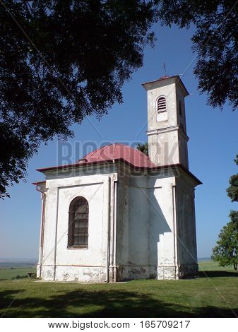 Picture of a small chaple standing on hill covered with trees