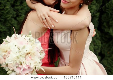 Luxury Bride Hugging Bridesmaid And Smiling, Joyful Moment At Reception, On Background Green Wall Of