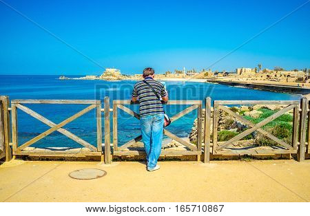 The young tourist overlooks the coast of Caesarea with its ancient landmarks Israel.