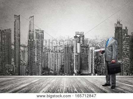 Headless engineer man with papers in hand against construction background