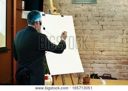 Elegant Speaker Lecturer Holding Marker At Empty White Board, At Meeting, Business Marketing Lecture