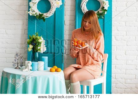 Young girl with tangerines in hands. The girl in the interior with tangerines